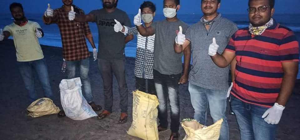 A group of people posing for a photograph after compleing the beach clean up drive in Visakhapantam